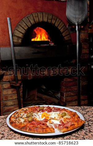 Ready-made pizza waiting in front of the oven