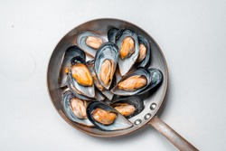 Ready mussels in a pan on a white background, sea mussels, the hand that holds the handle of the pan in which the mussels.