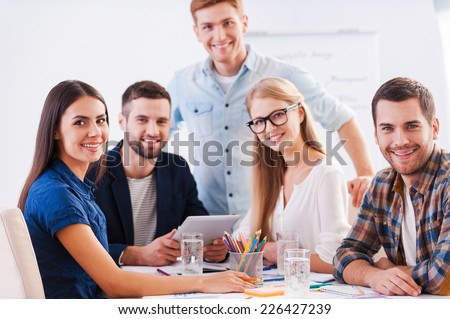 Ready to brainstorm. Group of happy business people in smart casual wear sitting together at the table and looking at camera #226427239