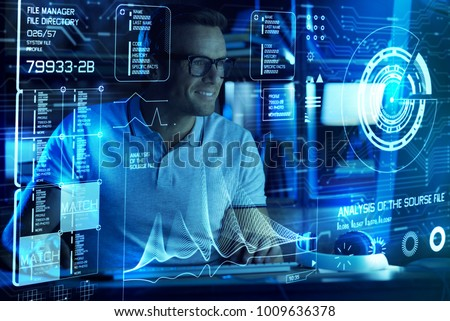 Ready to detect. Cheerful professional IT man smiling and coding while being involved in work