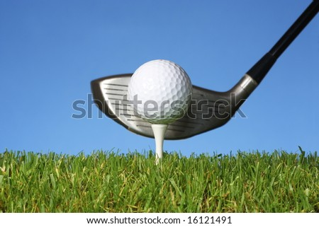 Ready to drive a golf ball off a tee with grass and a blue background.