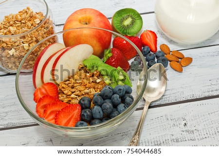Ready to eat healthy an nutritious breakfast - granola with strawberry, blueberry, almonds, apple and kiwi fruits and berries and a jar with milk nearby. Close-up capture, selective focus. #754044685
