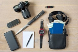 Ready-to-go spy kit. Photo camera, phone, powerbank, notepad with pen, knife, hand watch, USB memory stick, document bag with two passports and money in different currencies. Light wooden background.