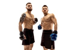 Ready to grow up. Two professional fighters posing isolated on white studio background. Couple of fit muscular caucasian athletes or boxers standing. Sport, competition and human emotions concept.
