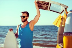 Ready to have some fun. Smiling young man holding skimboard and while opening a trunk door of his retro minivan with sea in the background