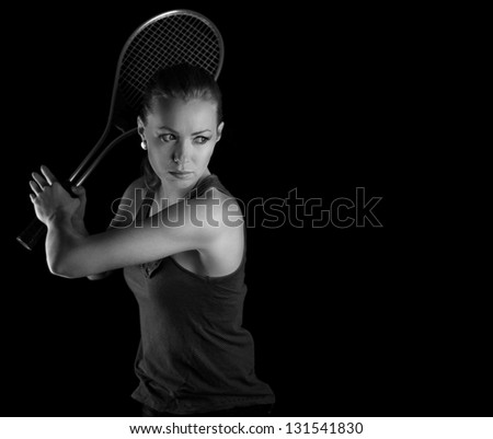 Ready to hit! Female tennis player with racket ready to hit a tennis ball. On black.