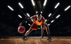 Ready to jump. African-american young basketball player in action and motion in flashlights over dark gym background. Concept of sport, movement, energy and dynamic, healthy lifestyle. Arena's drawned