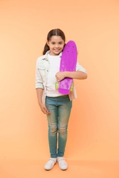 Ready to ride. Kid girl happy carries penny board. Child likes skateboarding with penny board. Modern teen hobby. How to ride skateboard. Girl happy face carries penny board yellow background.