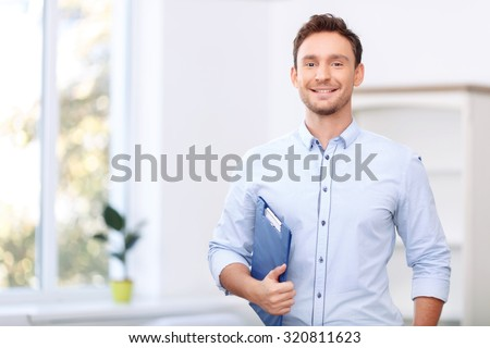 Ready to sale. Pleasant cheerful handsome realtor holding folder and expressing positivity while standing near window Stock photo ©