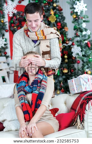Ready to take Christmas presents. Loving couple is in the festive Christmas living room. Young and pretty girl is sitting on the sofa with closed eyes, while her husband is behind her