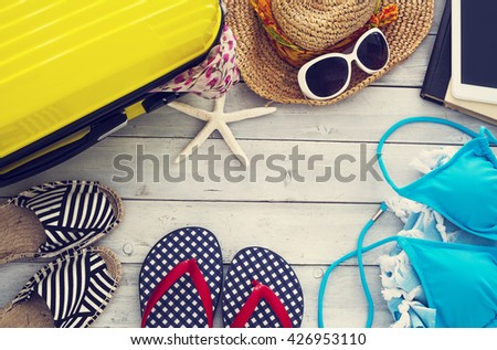 Ready vacation suitcase on wooden background
