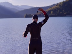 reak triathlon athlete getting ready and prepare goggles hat and  wetsuit for swimming training on lake