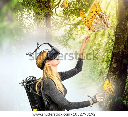 Real and virtual world on one image. young smiling woman in virtual reality glasses and equipment with sensors on head and hands in room and in mystery forest. full immersion #1032793192