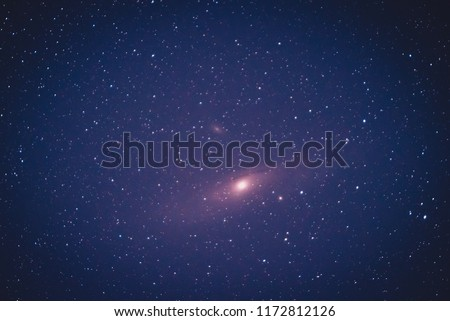 Real astronomical photo of andromeda galaxy taken with a 200mm camera on a clear sky with a long exposure. Stack of five pictures of andromeda galaxy.