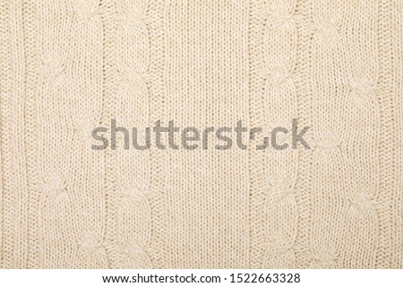 Real beige melange knitted fabric with cable pattern textured background