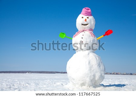 Real big snowman blue sky background - stock photo