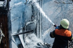 Real brave hero combat the fire with foam extinguisher. Strong and brave firefighter saving burning building. Firefighter work concept. Firefighter are using water in fire fighting operation