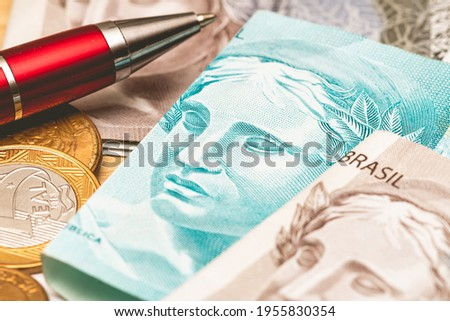 Real - BRL, money from Brazil. Dinheiro, Reais, Real Brasileiro, Brasil. Folded money notes of the Brazilian Real in macro photography on a table with a red pen and coins in the scene composition. Foto stock ©