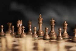 real chess pieces on a dark background made of quality boxwood wood. The beginning of a piece's game in its original position. Strategic chess game
