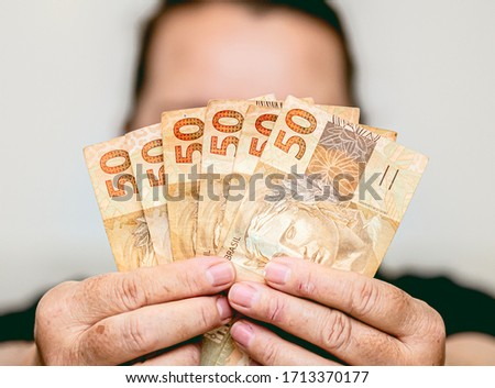 Real currency. Brasil, Dinheiro, Money, Reais. A Woman holding in hands a fifty Reais banknotes. Foto stock ©