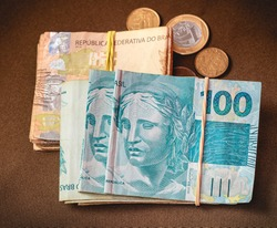 Real Currency, Brazil. Money notes of Brazilian currency on a table along with some coins.