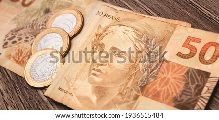 Real currency - BRL. Money from Brazil ( Dinheiro, Brasil, Reais ). A Brazilian Real banknote and coins on a wooden table. Close-up photo.  Foto stock ©