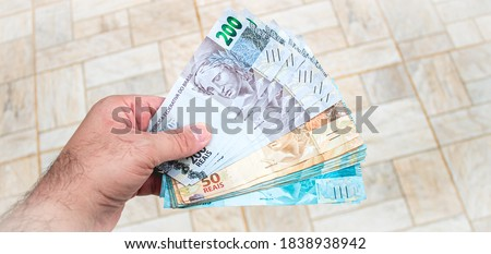 Real currency, money from Brazil. Brasil, Dinheiro, Reais, Hand. People holding in hand a brazilian banknotes. Foto stock ©