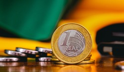 Real Currency, Money from Brazil. Dinheiro, Brasil, Reais, Moedas. Brazilian coins on a wood object. Economia Brasileira, investimentos, renda.