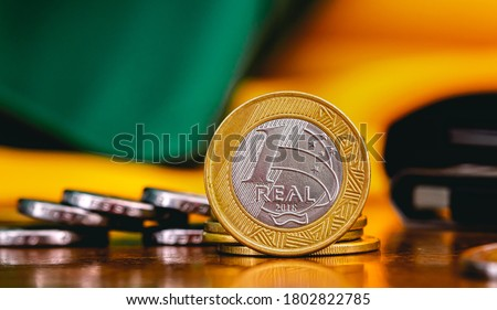 Real Currency, Money from Brazil. Dinheiro, Brasil, Reais, Moedas. Brazilian coins on a wood object. Economia Brasileira, investimentos, renda. Foto stock ©