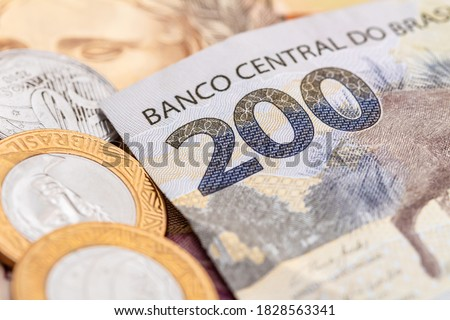 Real currency, Money from Brazil. Dinheiro, Reais, Brasil. A banknote of 200 reais and brazilian coins in close-up. Foto stock ©