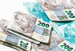 Real currency, money from Brazil. Dinheiro, Reais, Brasil. Brazilian banknotes of 200 reais and 100 reais in close up.