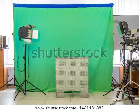 Real empty green screen (Chroma key) film/photo studio with lighting/studio equipment
