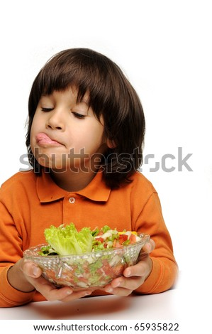Real enjoying fresh green salad, cute kid with tongue out of his mouth