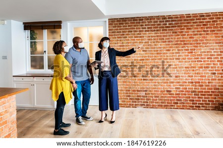Real estate agent and customer in face mask looking at a new project Сток-фото ©