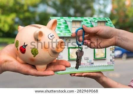 Real estate agent giving house keys to a new property owner, who is paying all saving money from piggy bank on blurred background