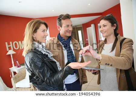 Real estate agent giving house keys to clients