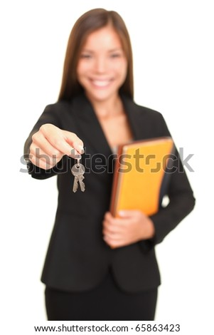 Real estate agent giving keys. Young realtor smiling handing over house keys to the new house owner, focus on keys. Isolated on white background.
