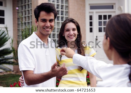 Real estate agent handing over house key to a happy couple