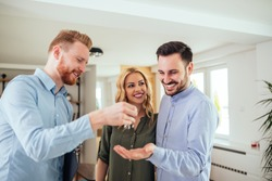 Real estate agent handing over the key to the happy couple