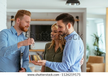 Real estate agent handing over the keys to the happy couple ストックフォト ©