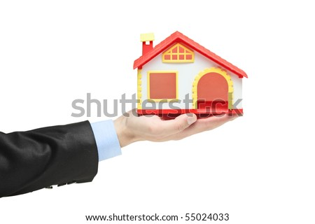 Real estate agent holding a model house in a hand isolated on white