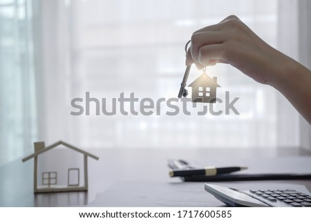 Real estate agent holding house key on house shaped keyring on table with house designs document, calculator, model house. Concept of Investment property.