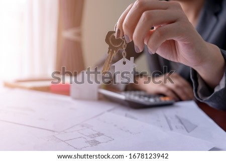 Real estate agent holding house key on table with house designs document,calculator,model house.Concept for real estate