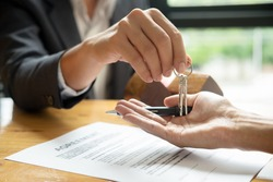 real estate agent holding house key to his client after signing contract agreement in office,concept for real estate, moving home or renting property