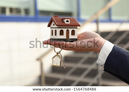 Real estate agent holding key and house model outdoors, closeup