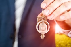 Real estate agent holding key of new apartment close up. realestate key real estate house security home deal concept