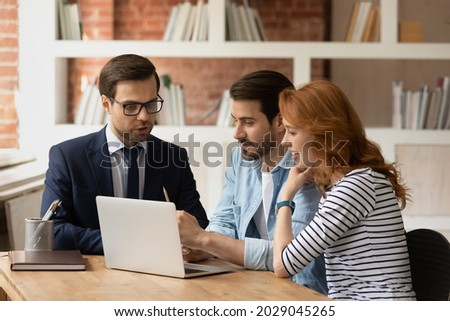 Real estate agent make offer for couple selects housing options, showing services presentation on laptop, choose new or secondary property for long term rental. Family and advisor discuss deal concept ストックフォト ©