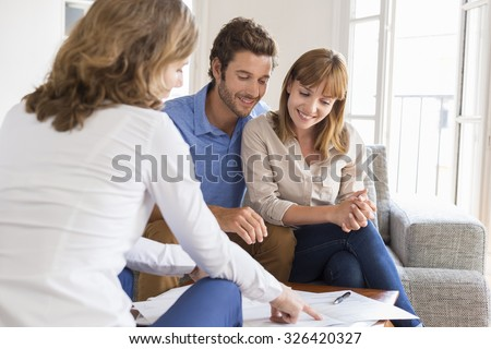 Real estate agent presenting a contract for house investment to futur owners couple