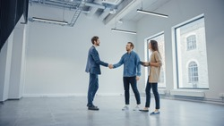 Real Estate Agent Showing a New Empty Office Space to Young Male and Female Hipsters. Entrepreneurs Meet the Broker and They Hand Shake. They Wish to Purchase or Rent.