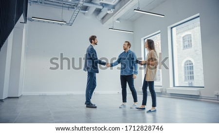 Real Estate Agent Showing a New Empty Office Space to Young Male and Female Hipsters. Entrepreneurs Meet the Broker and They Hand Shake. They Wish to Purchase or Rent. Foto stock ©